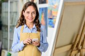 attractive female artist listening to music with smartphone in workshop and looking at camera