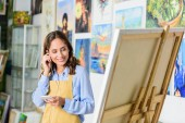 beautiful female artist listening to music with smartphone and looking at canvas in workshop