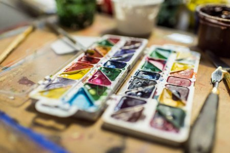 poster paints and watercolor paints on wooden table in workshop