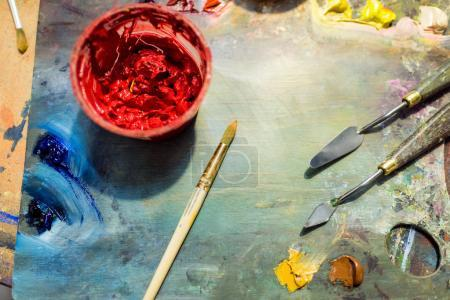 painting brushes, palette and red poster paint on wooden table in workshop