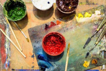 Photo pour Vue de dessus de pinceaux, palette et affiches peintures sur une table en bois en atelier - image libre de droit