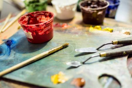 painting brushes, palette and poster paints on wooden table in workshop