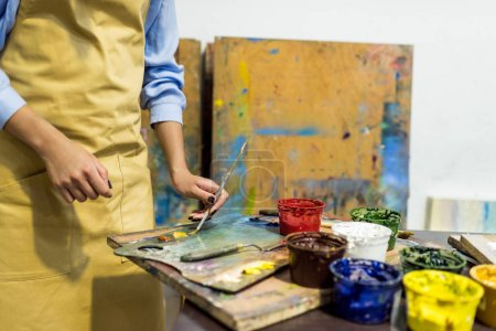 Photo for Cropped image of artist taking paint with brush from palette in workshop - Royalty Free Image