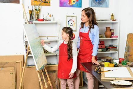 Photo for Teacher watching how pupil painting on canvas in workshop of art school - Royalty Free Image