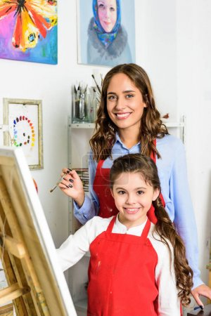smiling teacher and pupil painting together in workshop of art school