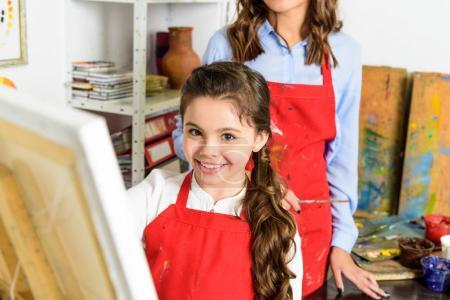 smiling pupil painting in workshop of art school