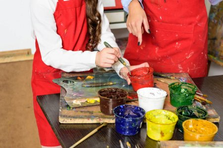 Photo for Cropped image of teacher and pupil taking poster paints in workshop of art school - Royalty Free Image