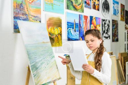 serious child standing with tablet in workshop of art school and pointing on canvas
