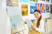 smiling child standing with tablet in workshop of art school and pointing on canvas