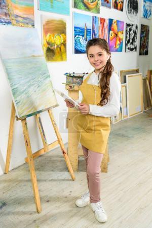 kid standing with tablet in workshop of art school