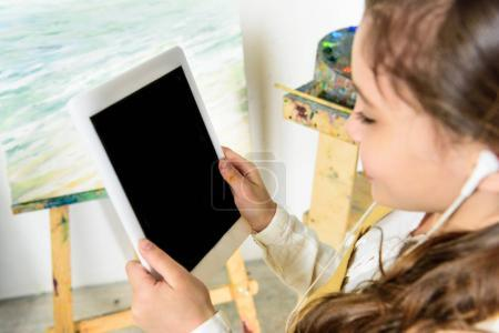 kid listening to music with tablet in workshop of art school