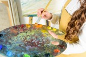 cropped image of child taking oil paints from palette in workshop of art school