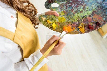 Foto de Recortar imagen de niño que pinturas al óleo de paleta en taller de escuela de arte - Imagen libre de derechos