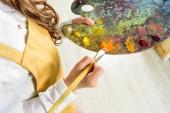 Cropped image de kid prenant des peintures à l'huile de la palette dans l'atelier de l'école d'art