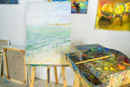 canvas on easel and paintings on wall in workshop