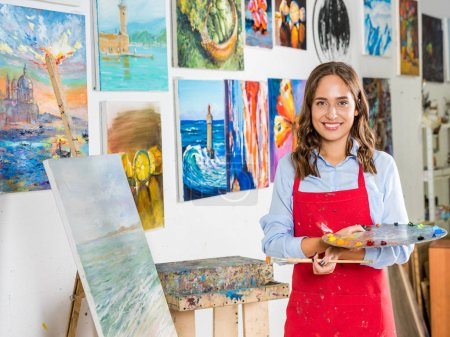 attractive female artist holding painting brush and palette near canvas in workshop