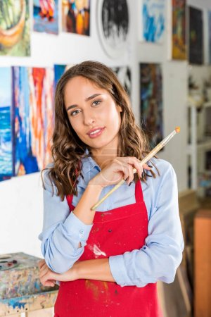 beautiful female artist holding painting brush in workshop