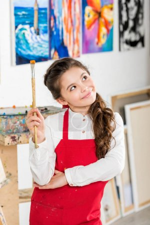 pensive kid holding painting brush and looking up in workshop of art school