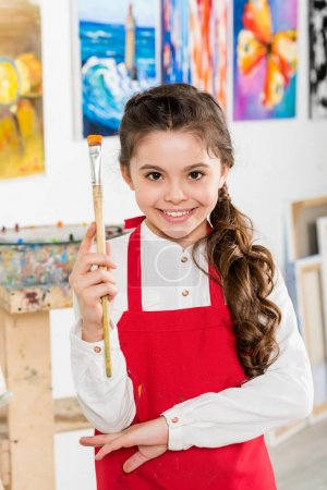 Photo for Smiling kid holding painting brush in workshop of art school - Royalty Free Image