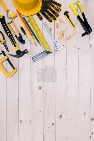 Top view of different tools on wooden tabletop with copy space