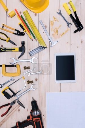 Top view of different tools with blueprint and digital tablet on wooden tabletop