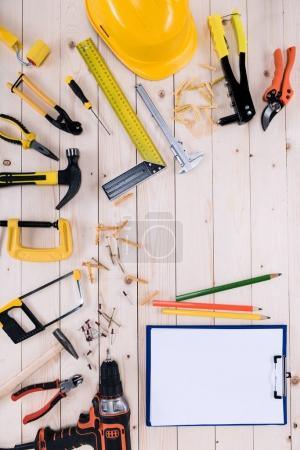 Top view of different tools with clipboard on wooden tabletop with copy space