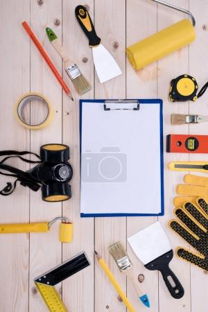 Top view of different tools with clipboard on wooden tabletop