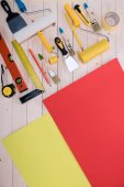 Top view of set of construction tools and colored paper on wooden table
