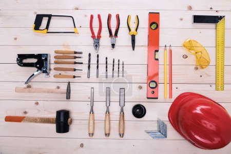 Photo for Top view of set of construction tools and hard hat on wooden table - Royalty Free Image