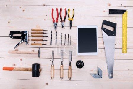 Vue de dessus de divers outils de construction et tablette numérique sur table en bois