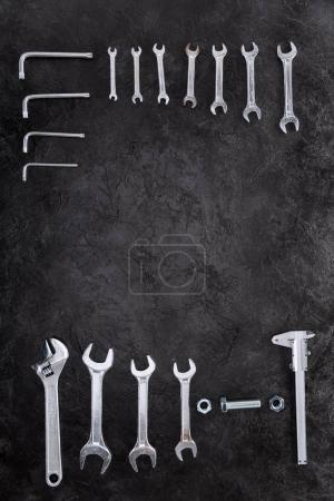 Top view of set of construction tools, wrenches and spanners on black