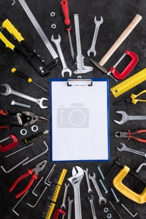 Top view of set of construction tools and blank clipboard