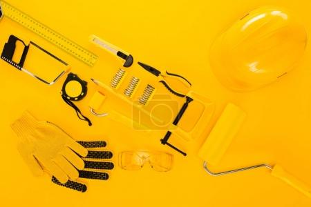 Top view of various work tools and equipment on yellow
