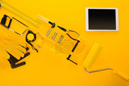 Top view of various work tools, equipment and digital tablet on yellow