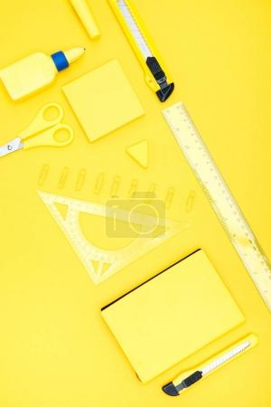 Photo for Top view of organized various office supplies on yellow - Royalty Free Image