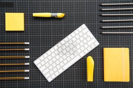 Photo for Top view of white keyboard and organized office supplies on black - Royalty Free Image