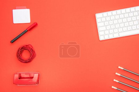 Photo for Top view of white keyboard and organized office supplies on red background - Royalty Free Image