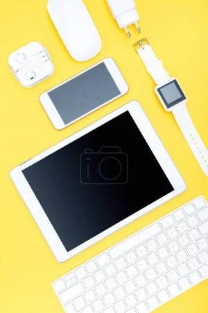 Photo for Flat lay of office supplies, keyboard, digital tablet, smartwatch and smartphone on yellow - Royalty Free Image
