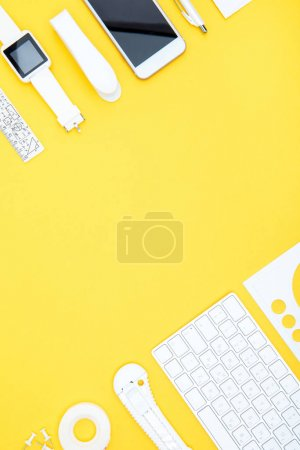 Photo for Flat lay of office supplies, digital devices with copy space on yellow - Royalty Free Image