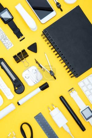 Photo for Flat lay of office supplies, digital devices and notepad on yellow - Royalty Free Image