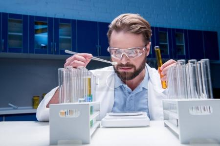 Photo for Bearded chemist in goggles with reagents in tubes and tablet in laboratory - Royalty Free Image