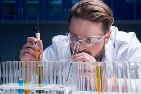 chemist in goggles with reagents
