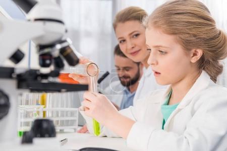 Photo pour Adorable petite fille avec des flacons en laboratoire, deux scientifiques derrière - image libre de droit