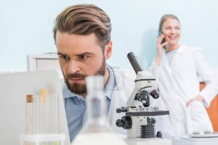 Photo for Concentrated bearded scientist working with microscope and laptop in laboratory - Royalty Free Image
