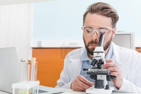Photo for Concentrated bearded scientist working with microscope in laboratory - Royalty Free Image