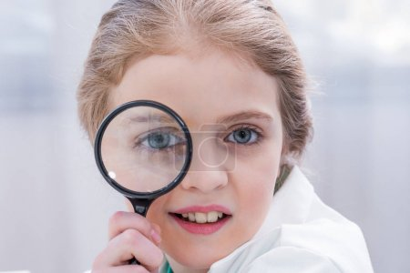 Little girl with magnifier