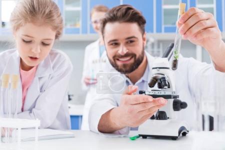 Photo pour Professeur barbu souriant et petit étudiant travaillant au microscope et au tube à essai en laboratoire - image libre de droit