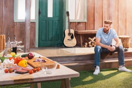 Photo pour Beau jeune homme barbu assis sur le porche et boire de la bière - image libre de droit