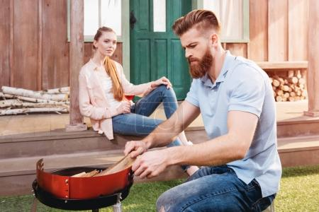 Photo for Smiling young woman drinking wine and looking at man kneeling near outdoor grill - Royalty Free Image