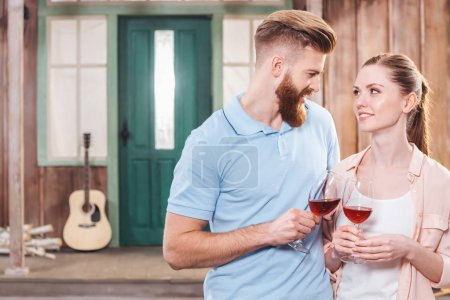 Photo for Happy man and woman embracing and holding wine in wineglasses - Royalty Free Image